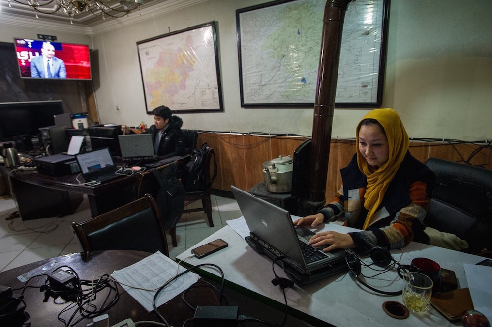 Journalist Freshta Farhang, who writes about women's issues for an online media outlet, sits on her desk in the newsroom, in Kabul, Afganistan, 13 February 2019, Scott Peterson/Getty Images